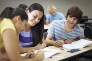 Portrait of young college friends studying together in classroom